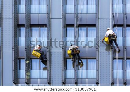 Three climbers wash windows and glass facade of the skyscraper  - stock photo