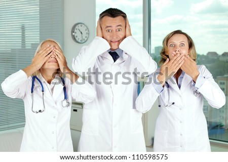 Three clinicians in white coats covering eyes, mouth and ears - stock photo