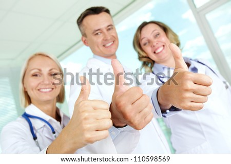 Three clinicians in white coats keeping thumbs up and looking at camera - stock photo
