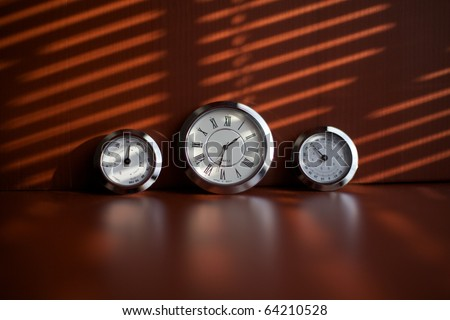 Three clocks on a brown table illuminated by the sun through the blinds. - stock photo
