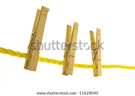 three clothespins hanging on a clothline on white background - stock photo