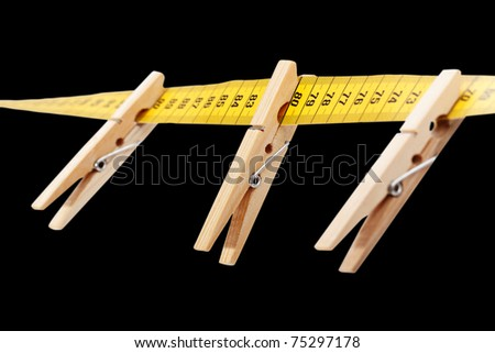 Three clothespins on the yellow measuring tape isolated a black surface. - stock photo