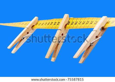Three clothespins on the yellow measuring tape isolated a blue  surface. - stock photo