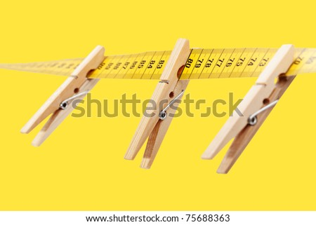 Three clothespins on the yellow measuring tape isolated a yellow surface. - stock photo