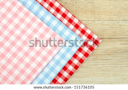 Three cloths with checks on a wooden table