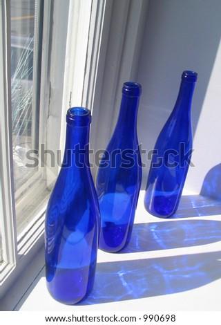 Three Cobalt Blue Bottles in Window - stock photo