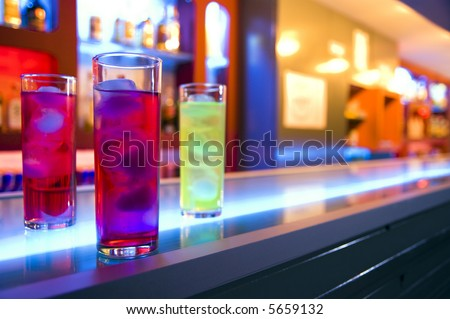 Three cocktail drinks on a bar, blurry color background - stock photo