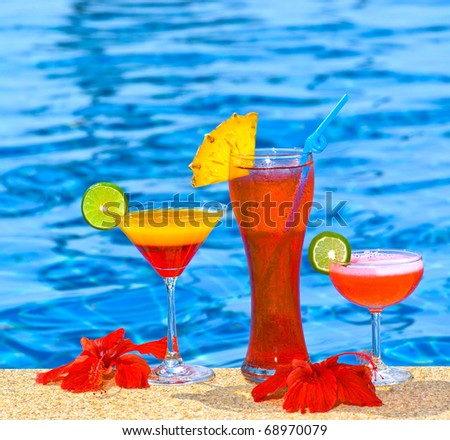 three cocktails near the pool - stock photo