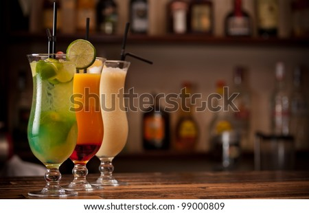 Three cocktails on a bar table - stock photo