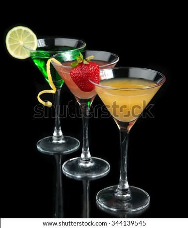 Three cocktails red cosmopolitan cocktails decorated with citrus lemon twist yellow martini drink with strawberry isolated on a black background