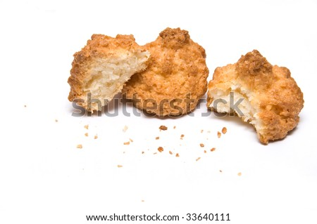 Three coco biscuits with bites and crumbs - stock photo