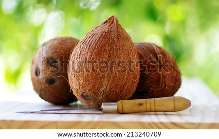Three coconuts and a knife - stock photo