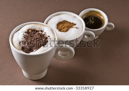 Three coffee cups with espresso, cappuccino, mochaccino over brown background - stock photo