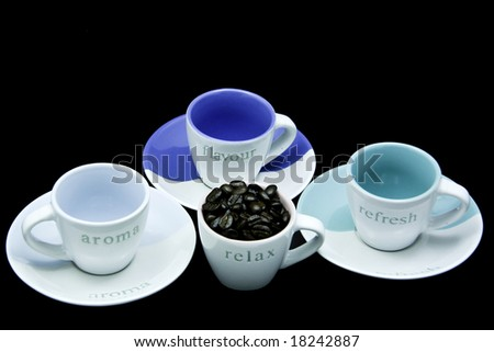 Three coffee cups with fresh coffee beans isolated on black background - stock photo