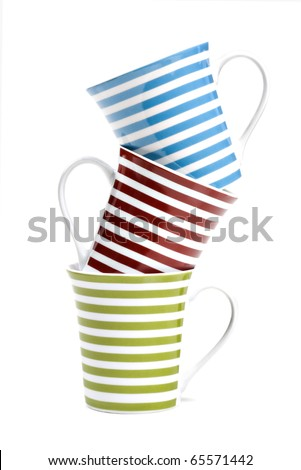 Three coffee mugs with red, green and blue stripes stacked up - stock photo