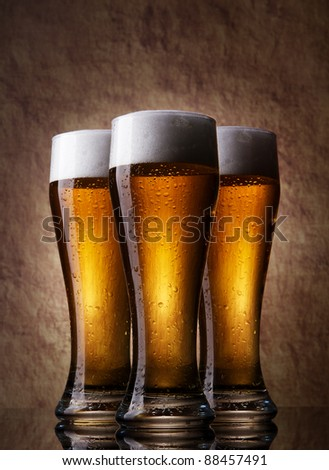 Three cold Beer into glass on a old stone