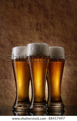 Three cold Beer into glass on a old stone - stock photo