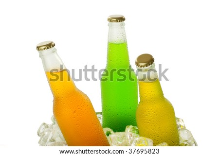 Three cold beverages in glass bottles on heap of ice cubes - stock photo