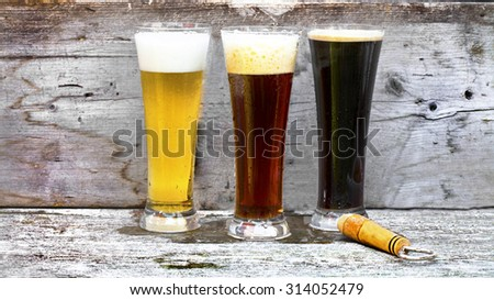 Three cold glasses of beer on a rustic bar.