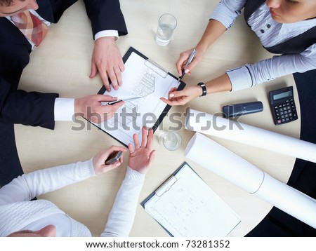 Three colleagues are discussing a round-table draft house - stock photo