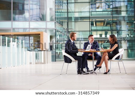 Three colleagues at a meeting in the foyer of a big business - stock photo