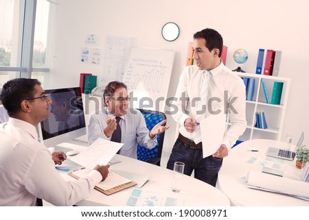 Three colleagues emotionally discussing business plan in the office - stock photo