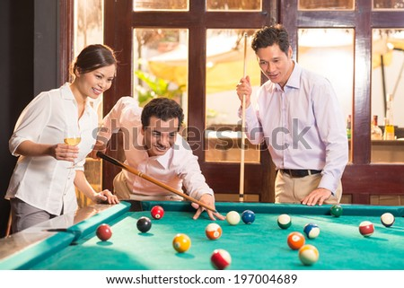 Three colleagues playing billiards after work - stock photo