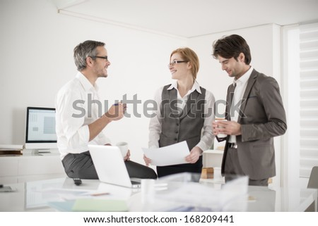 three colleagues speaks about business at office