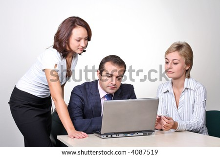 Three colleagues working at a computer