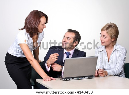 Three colleagues working at a computer.