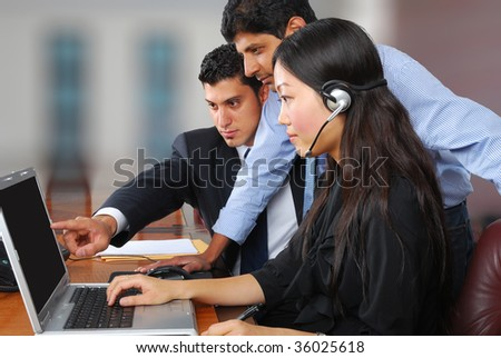 three colleagues working on a laptop - stock photo
