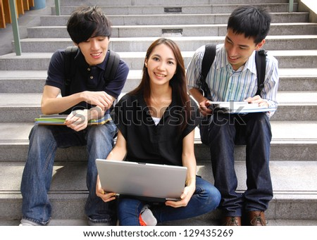 Three college friends sitting holding laptop with books on campus - stock photo