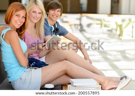 Three college student friends with tablet smiling looking at camera - stock photo