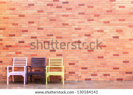Three color of chairs with a brick - stock photo