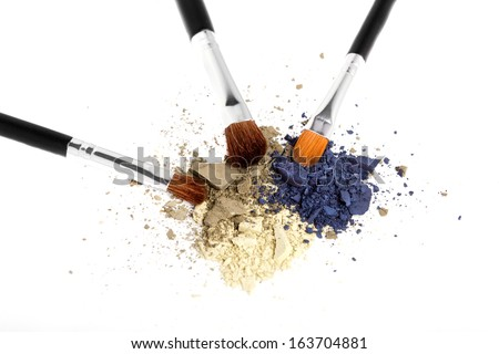 Three-color powder eyeshadow with three brushes on white background