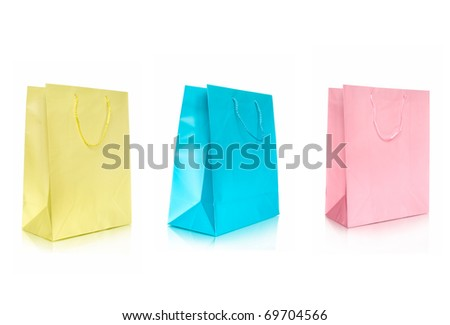 three color shopping bags in row isolated on white - stock photo