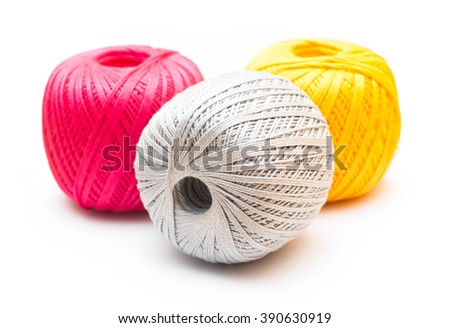 Three colored balls of knitting yarn on white background.