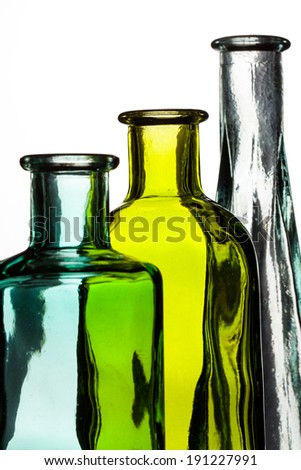 Three colored bottles, blue, yellow and clear on a white background. Bottles are aligned by height, shortest to tallest. - stock photo