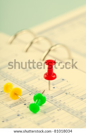 three colored buttons on an open notebook - stock photo