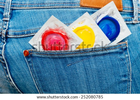 Three colored condoms in a jeans pocket. - stock photo
