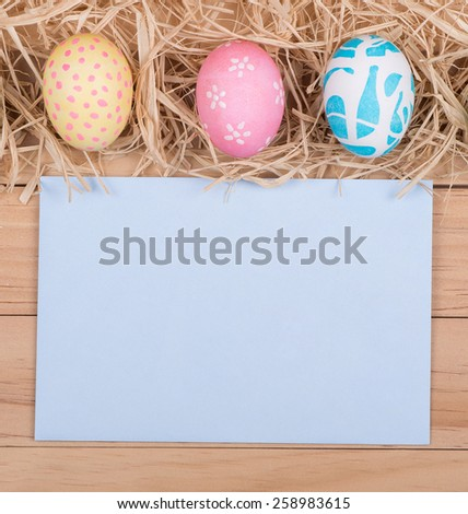 Three colored Easter eggs bordering a blank envelope - stock photo