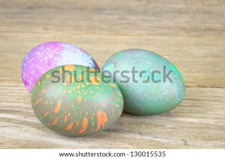 Three colored Easter eggs on an aged wood surface - stock photo