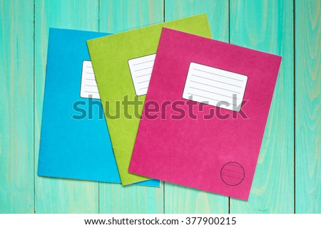 Three colored exercise books on the blue wooden background - stock photo
