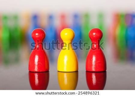 Three colored ludo figures in front of many others.  Two red and one yellow in a row. Figures in the background unsharp.Bokeh. - stock photo