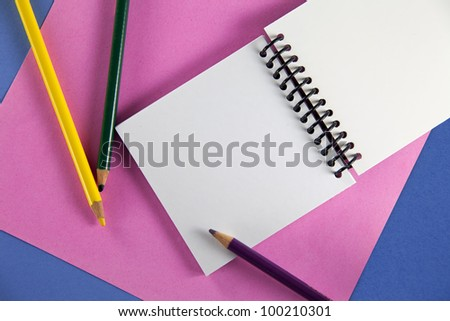 Three colored pencils with petite spiral notebook on pink and blue paper - stock photo