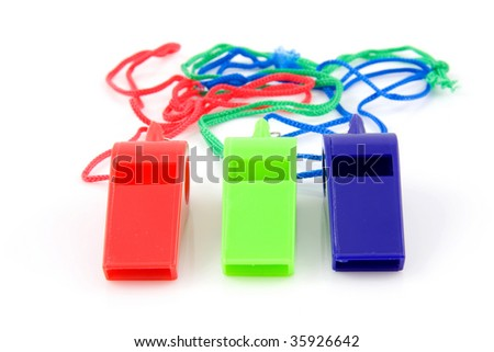 three colored plastic whistles isolated on white background