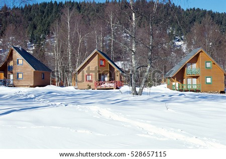 Three colored wooden chalets and winter snow, in La Feclaz, Savoy, France