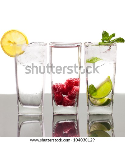 Three colorful alcoholic drinks with berries, fruit and ice. On a table with reflection and isolated over white. - stock photo