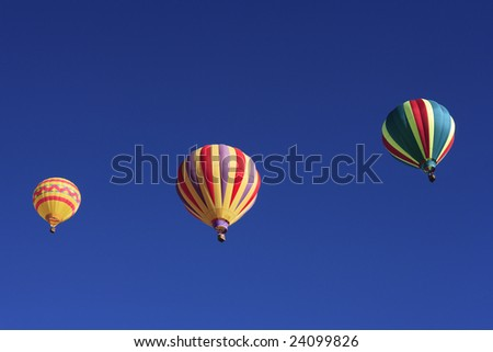 Three colorful balloons floating against a blue sky.