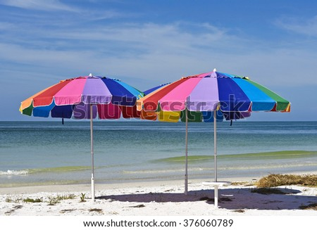 Three colorful Beach Umbrellas on a Sandy Beach with the ocean and sky in the background - stock photo